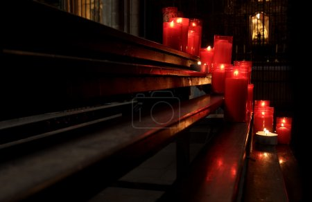 Photo pour Bougies dévotionnelles flamboyantes dans l'obscurité d'une église espagnole - image libre de droit