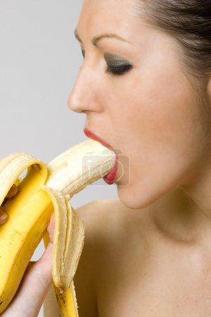 Young woman eating banana