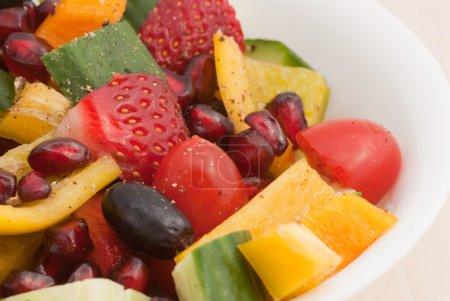 Photo pour Un bol de fruits frais et salade de légumes, arrosée avec vinaigrette de poivre noir - image libre de droit
