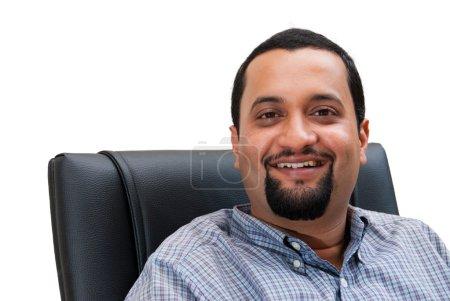 Photo pour Un homme d'affaires indien assis sur une chaise - isolée sur blanc - image libre de droit