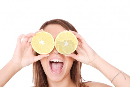 Photo pour Modèle heureux de manger une orange sur fond blanc - image libre de droit