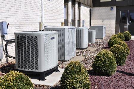 Photo pour Plusieurs grandes unités de climatisation de taille industrielle assises à l'extérieur d'un bâtiment en brique . - image libre de droit