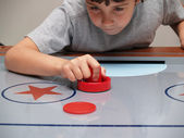 Young boy playing air hockey