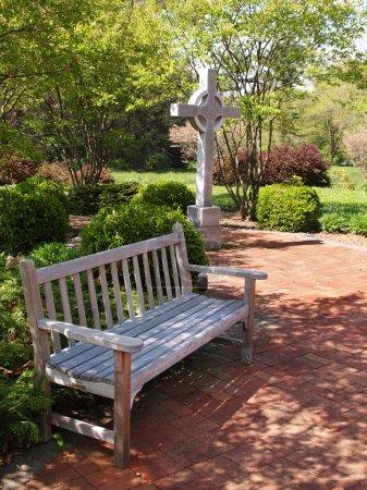 Photo pour Un banc en bois vide par un patio en brique rouge et une croix - image libre de droit