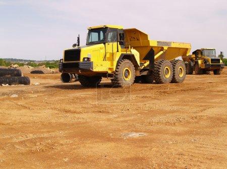 Photo pour Un camion à benne jaune près d'un chantier - image libre de droit