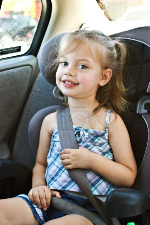 Photo for Little girl in a car seat smiling at the camera - Royalty Free Image