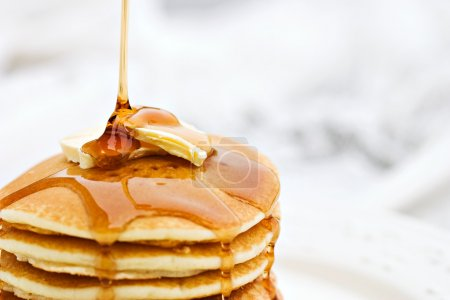Photo for Maple syrup pouring onto pancakes. Shallow DOF with focus on syrup and butter. - Royalty Free Image