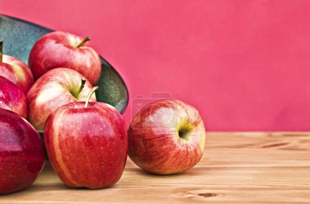 Photo for Red apples spilling from a bowl with copy space. - Royalty Free Image
