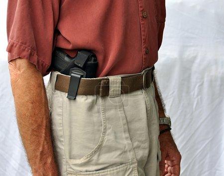 Photo pour Gros plan de l'arme de poing dans l'étui de port discret - image libre de droit