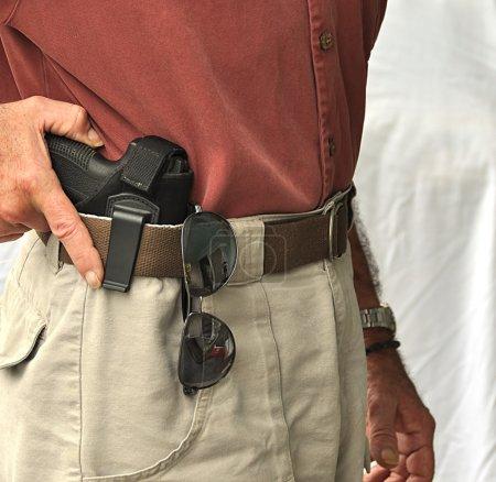 Photo pour Gros plan du pistolet dans l'étui de ceinture dissimulé - image libre de droit
