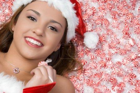 Photo pour Femme de Noël couchée dans des bonbons à la menthe poivrée - image libre de droit