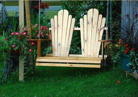 Foto de Primer plano de una silla columpio de madera en el jardín de flores - Imagen libre de derechos