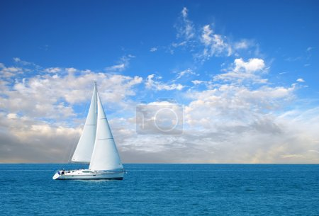 Modern sail boat on a sunny day with clouds in the sky