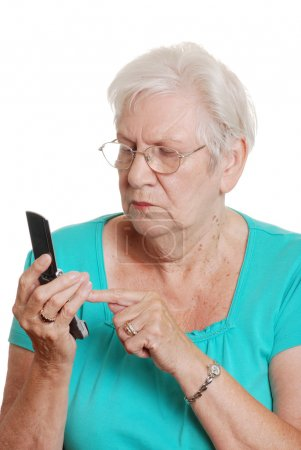 Senior woman dialing number cell phone