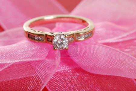 Closeup diamond ring on pink lace