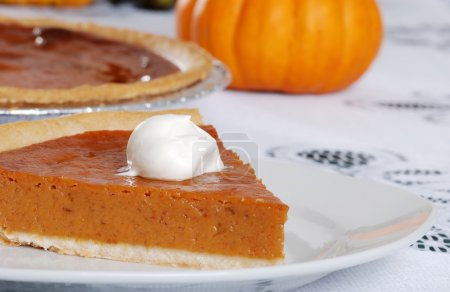 Closeup pumpkin pie slice and whip cream