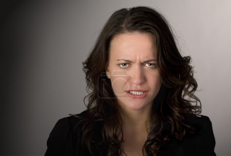 Photo for Emotional portrait of a frustrated woman against dark background - Royalty Free Image
