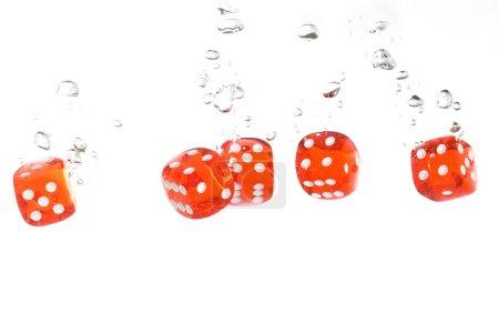 Photo pour Dés transparents rouges tombant dans l'eau claire - image libre de droit
