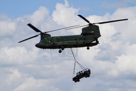 A chinook helicopter carrying a jeep