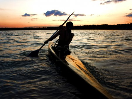 Kayaker against sunset