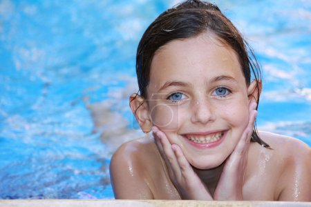 Foto de Una chica guapa con ojos azules, relajarse en una piscina sonriendo y mirando a cámara - Imagen libre de derechos