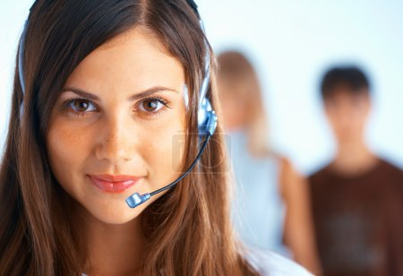 Photo for Young beautiful woman with headset with some at the background - Royalty Free Image