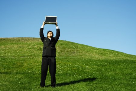 Photo for Happy businessman holding laptop high in the air - Royalty Free Image