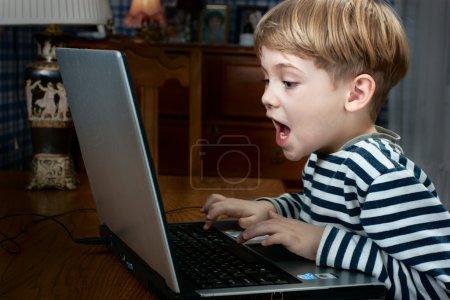 Photo pour Petit garçon jouant le jeu d'ordinateur très émotionnel - image libre de droit