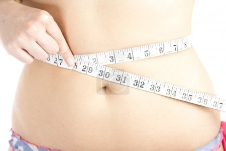 Woman measuring her belly with tape measure...