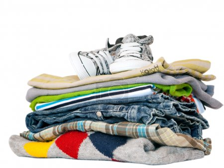 Photo for Pile of colourful boys clothes and sneakers isolated on white background. - Royalty Free Image