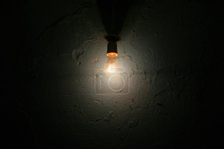 Photo for Light bulb hanging on the black wall - Royalty Free Image