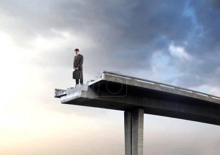 Photo for Portrait of a businessman standing on an interrupted highway bridge and looking into the empty space underneath - Royalty Free Image