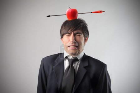 Photo for Portrait of a businessman with an apple pierced by an arrow on his head - Royalty Free Image