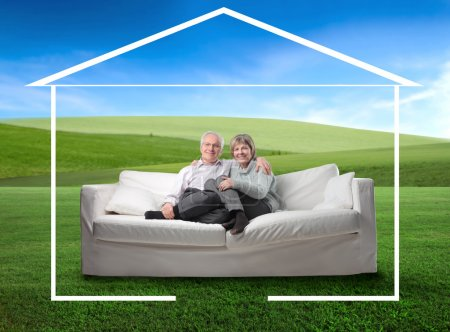 Photo for Portrait of a senior couple sitting in a couch on a green meadow and surrounded by the form of a house - Royalty Free Image