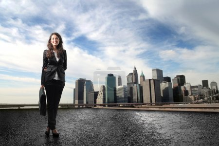 Photo for Portrait of a smilin young businesswoman standing in a cityscape - Royalty Free Image