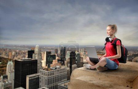 Photo pour Portrait d'une jeune femme assise au sommet d'un gratte-ciel avec un ordinateur portable sur ses genoux - image libre de droit