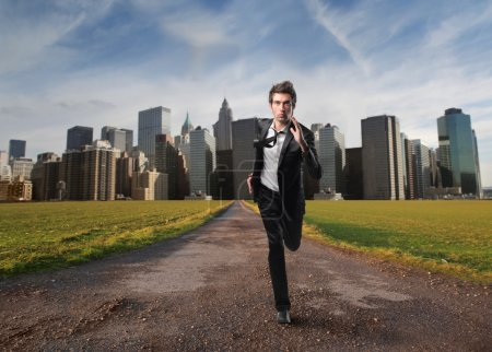 Photo for Portrait of a businessman running away from a city - Royalty Free Image