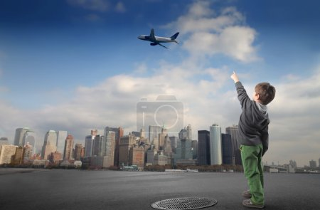 Photo for Portrait of a child pointing at an airplane flying over a city - Royalty Free Image