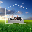 Smiling family sitting on a sofa on a green meadow surrounded by the form of a house