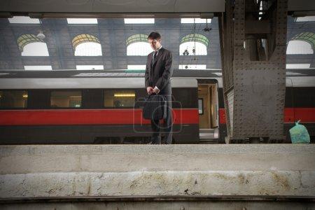 Photo pour Homme d'affaires, debout sur la plate-forme d'une station de train - image libre de droit