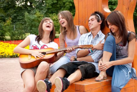 Four young friends play the guitar