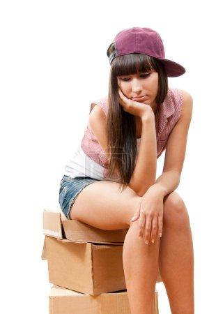 Sad girl sitting on cardboard boxes