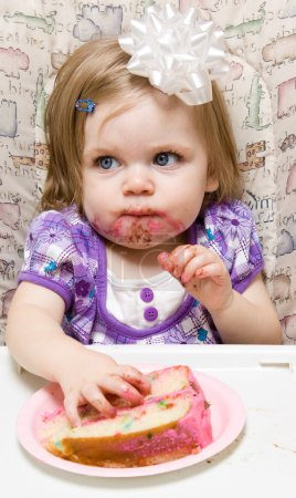 Photo for Girl eating a slice of cake and making a mess - Royalty Free Image