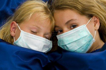 Photo pour Deux filles avec des masques protecteurs malades au lit - image libre de droit
