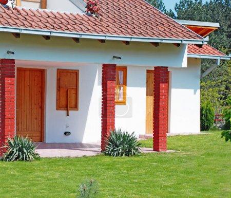 Photo pour Fragment du toit de la petite maison carrelée et jardin - image libre de droit