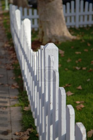 Photo for White picket fence in perspective bordered by sidwalk and yard - Royalty Free Image