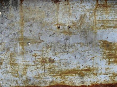 Photo pour Gros plan d'un panneau en métal peint avec boulons, rayé, peeling et rouillé. - image libre de droit