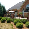 Large brick patio with an iron railing on the back...