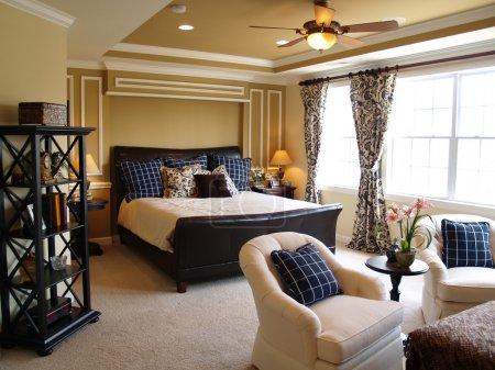 Photo pour Joliment décoré chambre principale dans une maison de luxe récemment construit. Il y a un lit traîneau en cuir noir, le mobilier sombre, la lumière en streaming à travers les fenêtres et une li - image libre de droit