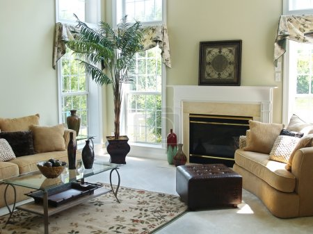Photo for A well decorated family room in a modern american home with an overstuffed sofa, chair and glass coffee table. Large windows make the room very bright and airy. - Royalty Free Image